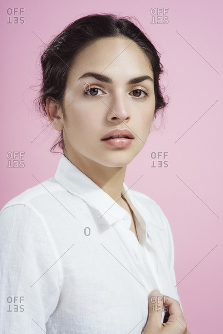 Woman with fresh dewy skin natural makeup white collared shirt looking at camera