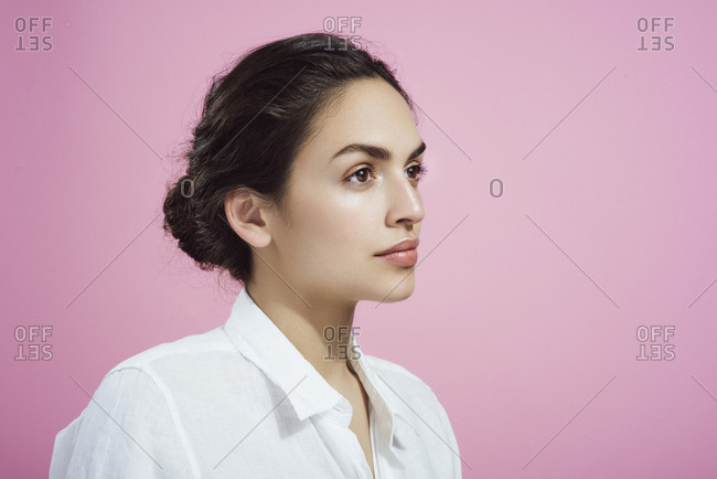 Woman with fresh dewy glowing skin natural makeup white collared shirt looking away