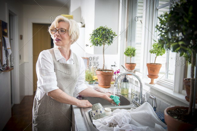 Mature blond woman prepping to cook in country kitchen