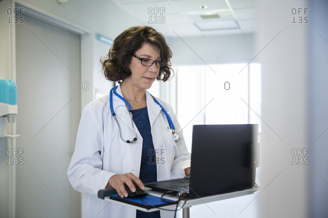 Mature female doctor using laptop  n hospital corridor