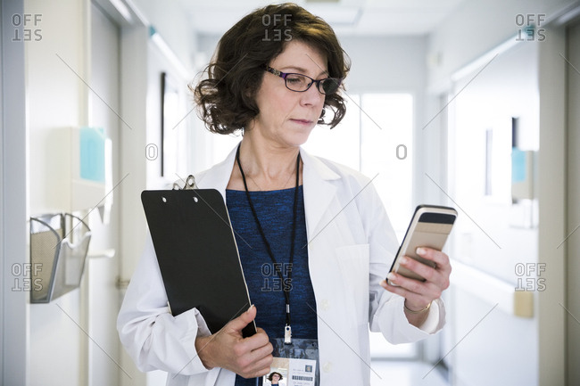 Mature female doctor holding clipboard while using mobile phone in hospital corridor