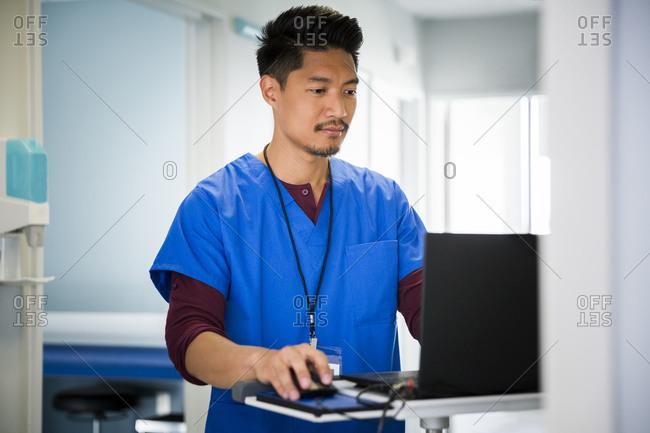 Mid adult male nurse using laptop in hospital corridor