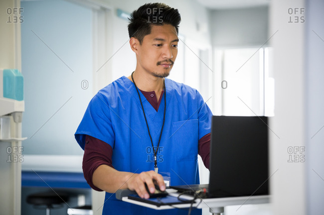 Mid adult male nurse using laptop in hospital corridor