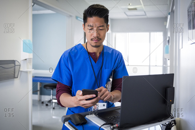 Mid adult male nurse using mobile phone by laptop in hospital corridor