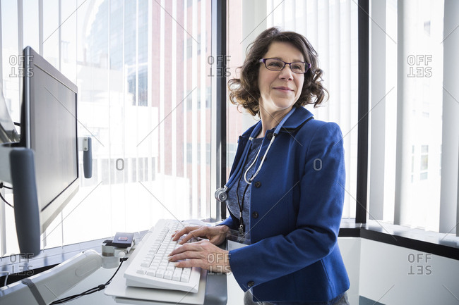 Mature female doctor using computer in examination room at hospital