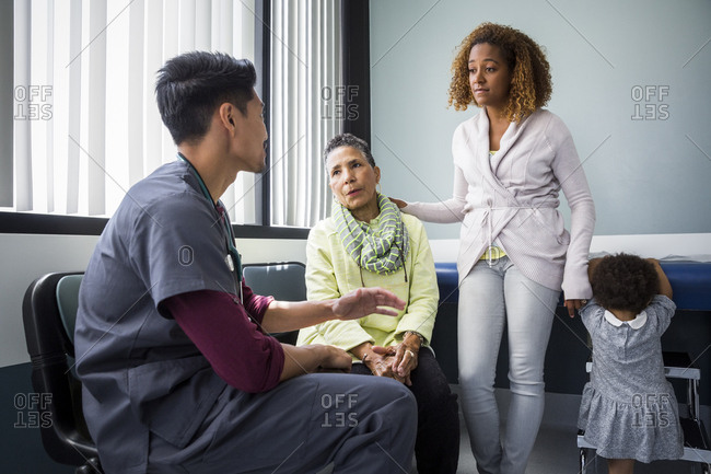 Mid adult male nurse talking with family in examination room at hospital