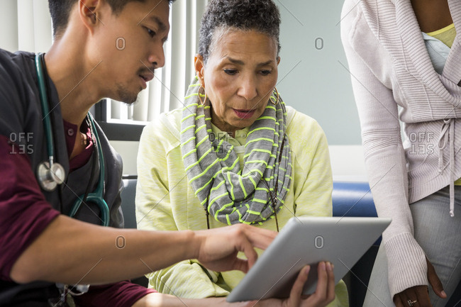 Mid adult male nurse showing digital tablet to senior woman by daughter in hospital