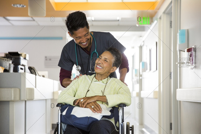 Smiling male nurse pushing senior female patient in wheelchair at hospital