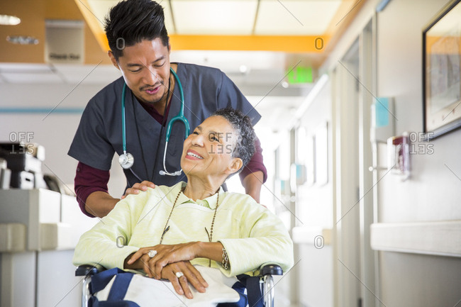 Male nurse talking with senior woman in wheelchair at hospital