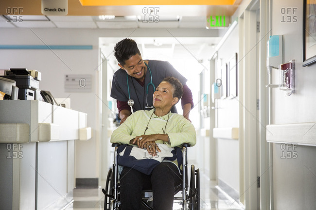 Happy mid adult male nurse pushing senior woman in wheelchair at hospital