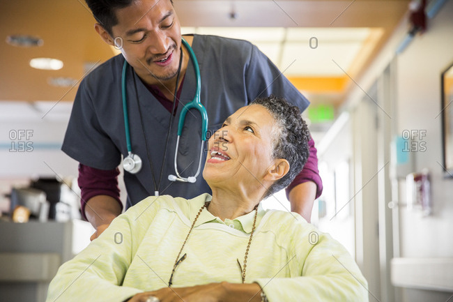 Mid adult male nurse talking to senior woman in wheelchair at hospital
