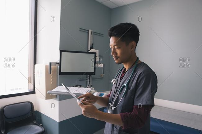 Mid adult male nurse using digital tablet in examination room at hospital