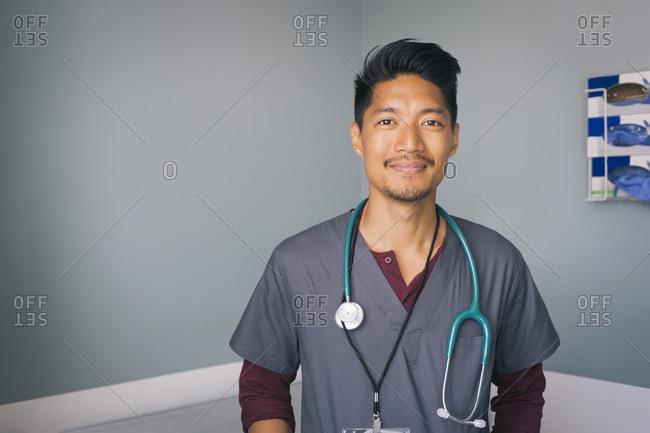 Portrait of confident male nurse wearing scrubs