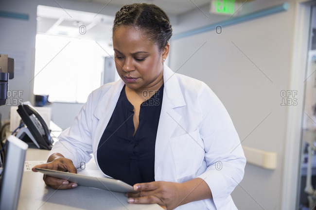 Mid adult female doctor looking at digital tablet in hospital