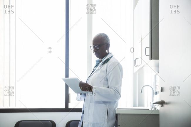 Senior female doctor using digital tablet in examination room