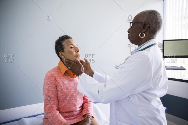 Senior female doctor examining glands in neck of patient