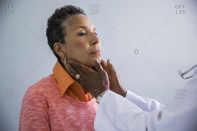 Cropped image of female doctor examining senior patient's neck in exam room