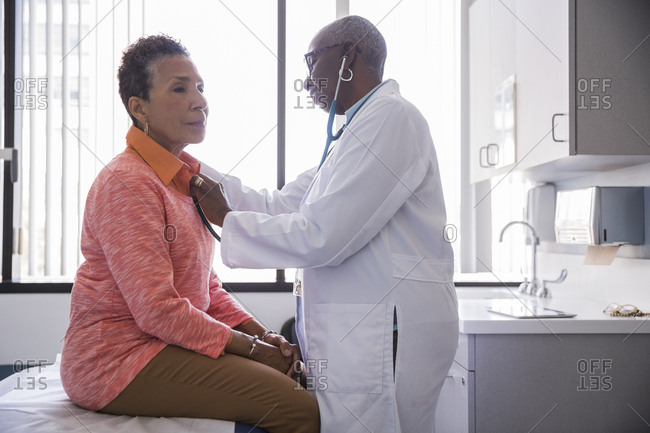 Doctor examining senior patient with stethoscope in examination room at hospital