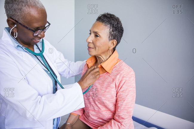 Female doctor examining senior patient with stethoscope in examination room at hospital