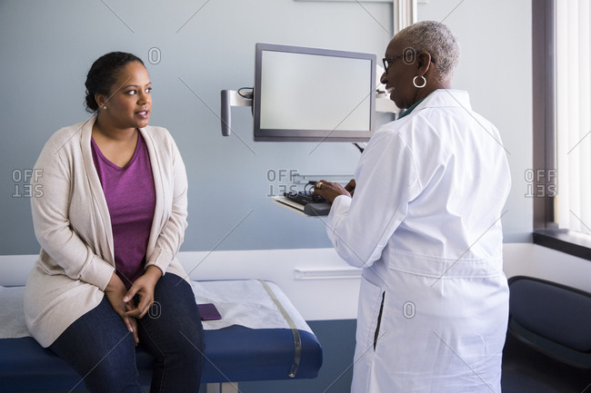 Mid adult female patient talking with senior doctor in examination room