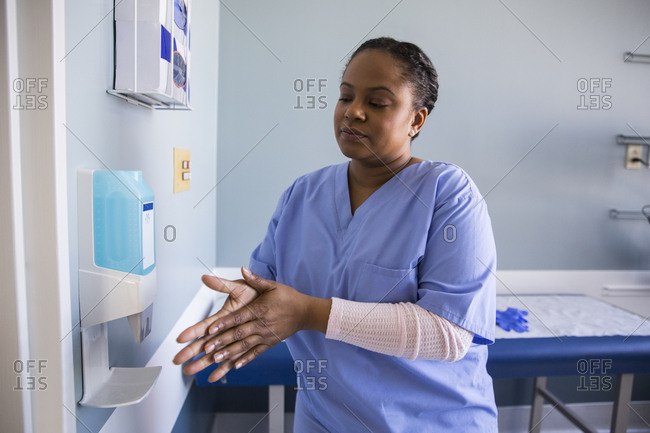 Mid adult female surgeon disinfecting her hands in examination room at hospital