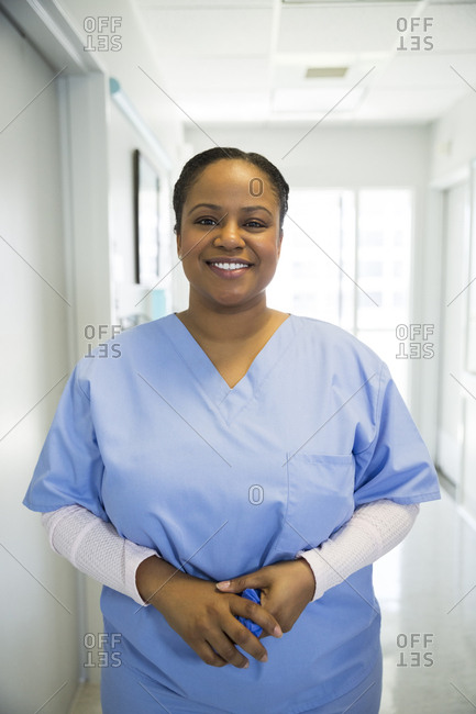Portrait of smiling mid adult female surgeon standing in hospital corridor
