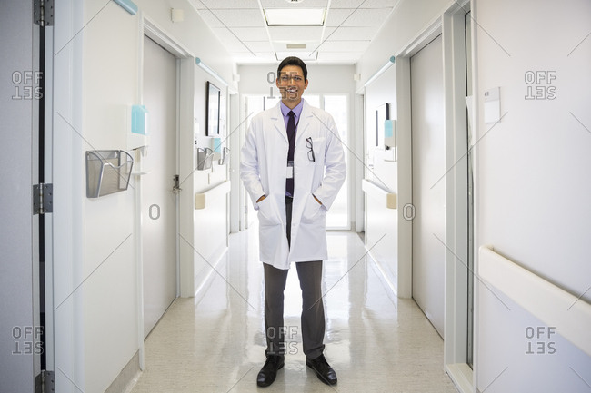 Full length portrait of confident male doctor standing in hospital corridor