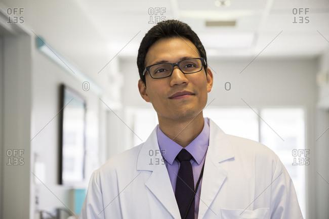 Portrait of mid adult male doctor wearing eyeglasses in hospital corridor