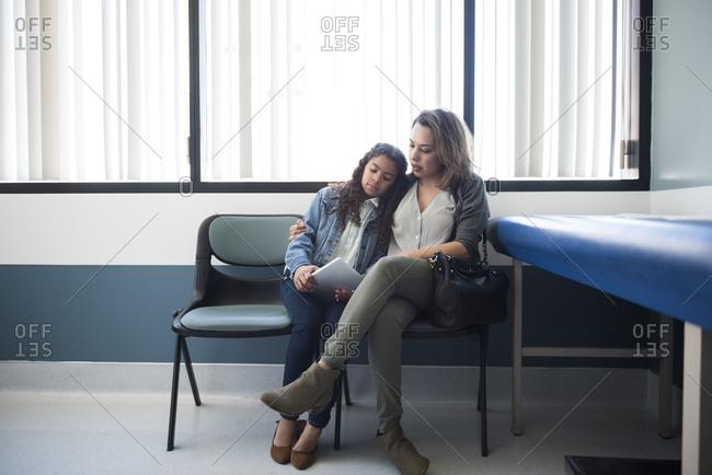 Mid adult mother sitting arm around daughter on chair in hospital exam room