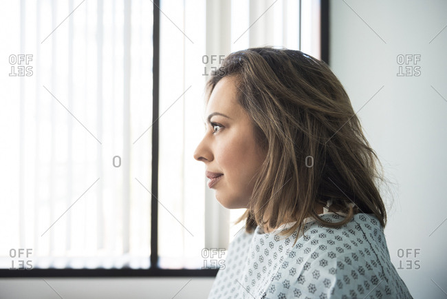 Side view of thoughtful mid adult female patient in hospital