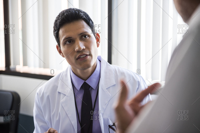 Mid adult male doctor listening to senior patient in examination room