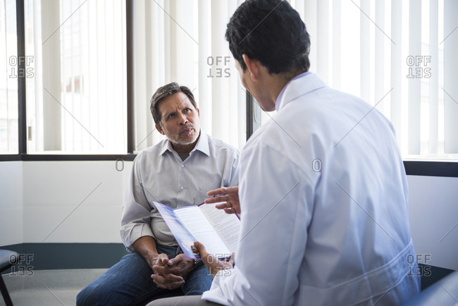 Mid adult doctor holding brochure while talking to senior male patient