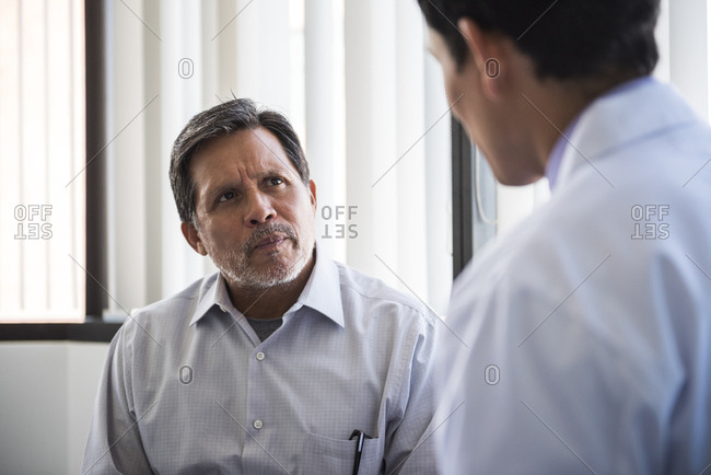 Senior male patient looking at doctor in examination room at hospital