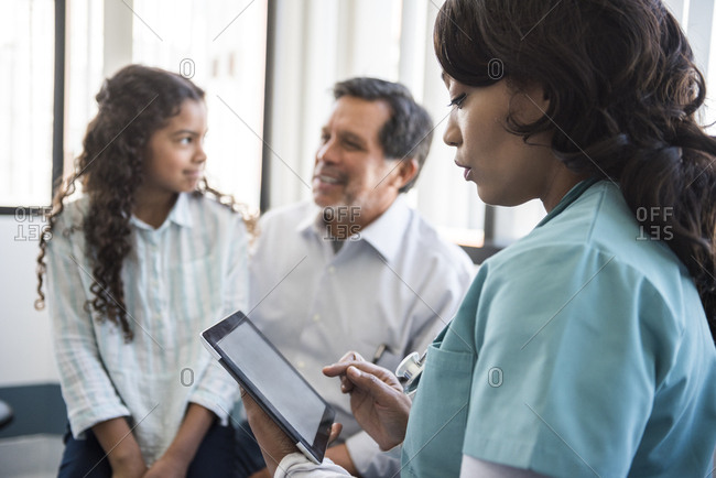 Mature female nurse using digital tablet with family in background at hospital