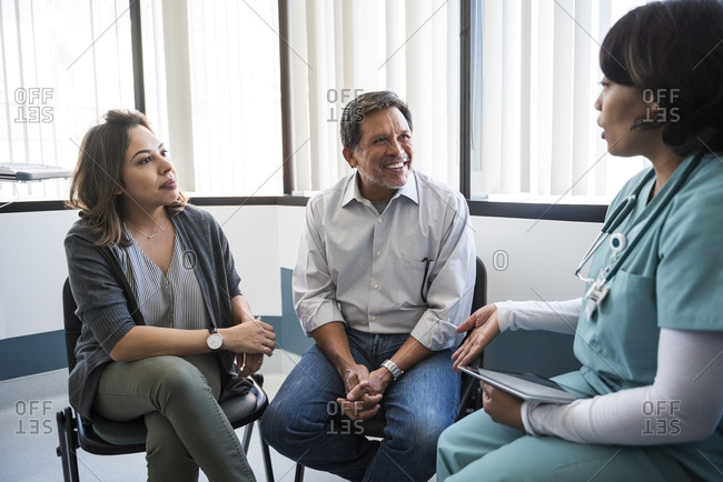 Mature female nurse talking with family in examination room at hospital