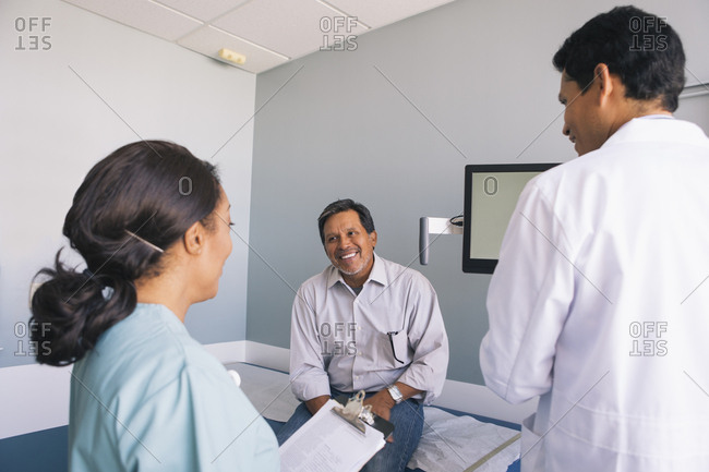 Smiling senior male patient with doctor and nurse in examination room at hospital