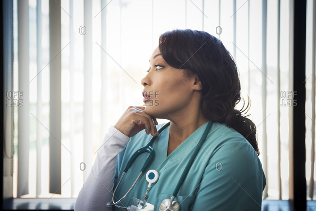 Thoughtful mature female nurse with stethoscope around neck in hospital