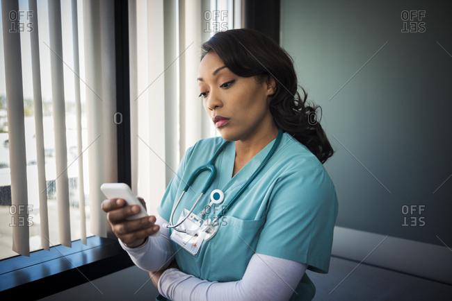 Mature female nurse using mobile phone