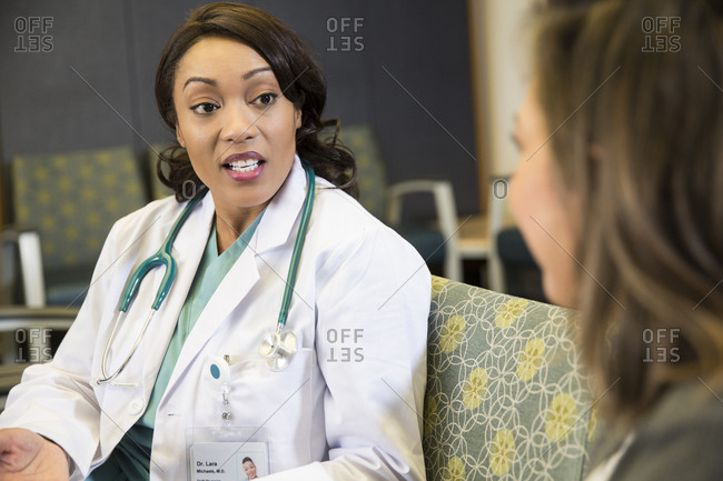 Mature doctor talking with female patient in hospital waiting room
