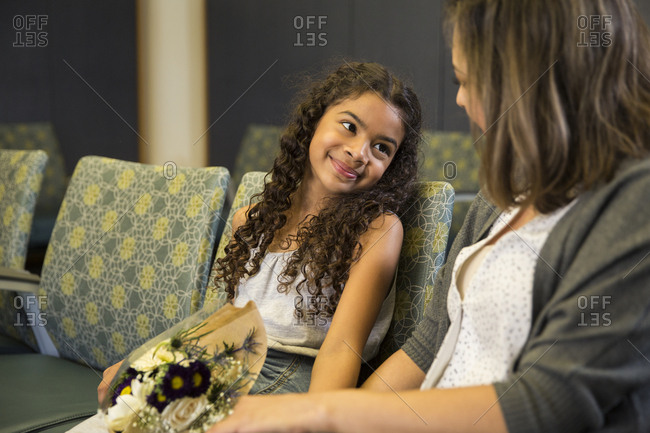 Smiling daughter looking at mother in waiting room at hospital
