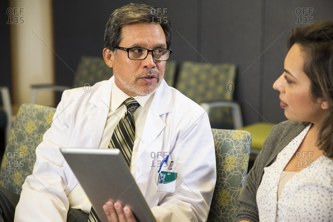 Senior male doctor talking with female patient while holding digital tablet in hospital waiting area