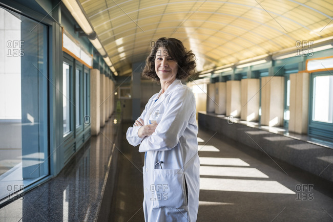Portrait of smiling mature doctor standing arms crossed in hospital corridor