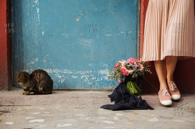 Woman and cat by flowers against wall