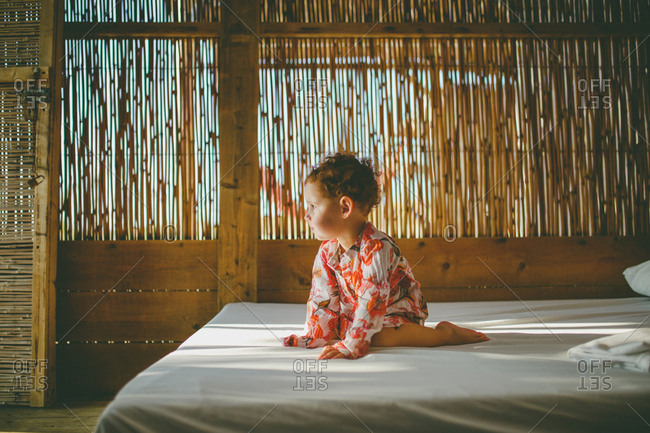 A girl sitting on a bed inside a beach hut wearing galbia