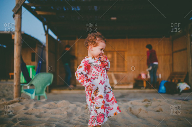 A girl standing outside her beach hut wearing galbia