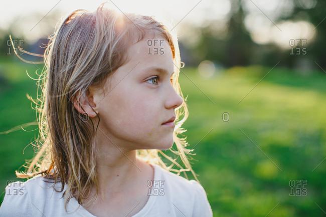 Girl backlit by sun in rural yard