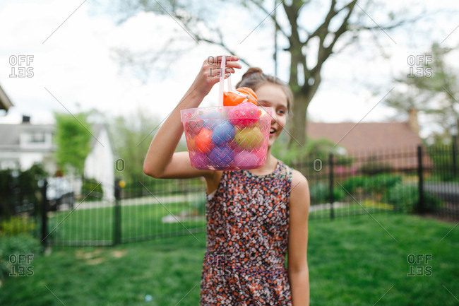 Girl with Easter egg basket in yard