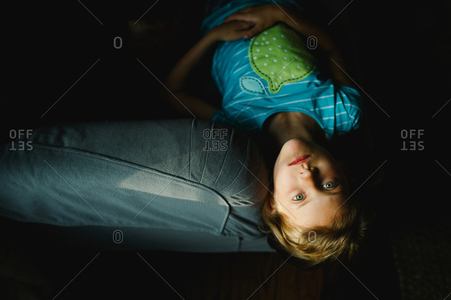 Girl lying on bed in shadows