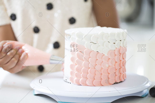 Pastry chef decorating a pink and white cake