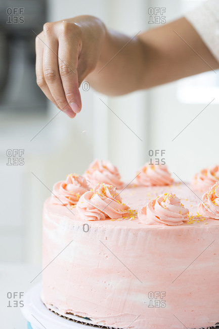 Pastry chef scattering sprinkles on cake